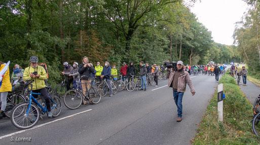 Wim Deekens von Gut Hahn (nicht im Bild) erläutert hier den Demonstranten die  Zerstörung eines Teils seines Waldes und die unvorstellbar bis zu 16 m hohe Brückenkonstruktion für die Autobahn über die Kreisstrasse