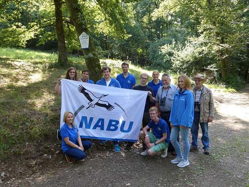 Vorstandsmitglieder der NABU-Gruppe Daaden stehen mit den StudentInnen vor einer NABU-Fläche bei Daaden