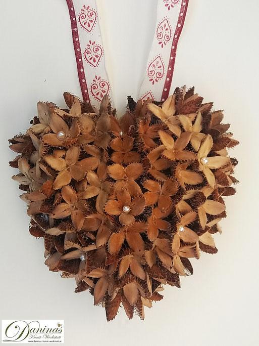 Handgefertigtes Bucheckern-Herz mit Perlen und ecru-rotem Zierband. Ideal als Geschenk, Herbst- oder Weihnachtsdeko. Mehr selbstgemachte Dekoartikel aus Naturmaterialien finden Sie auf meiner Website.