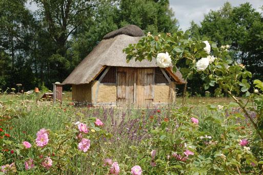 ein altes reetgedecktes fachwerkgebaäude steht inmitten von Blumen
