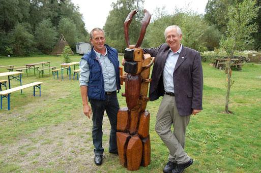 Der Holzskulturen-Künstler Hans-Jürgen Pille (links) aus Damme schenkt dem Naturschutz-Zentrum Dammer Berge und dem NABU Damme eine Hirschkäfer-Plastik. Riesig freut sich Werner Schiller. Foto: Frye 2011