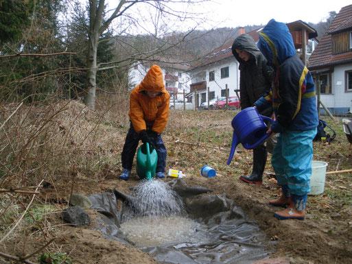 Der Tümpel wird mit Wasser befüllt.