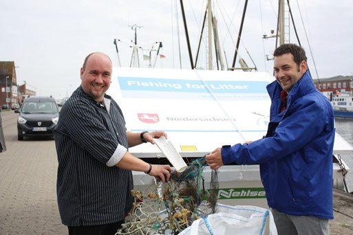 """Krabbenfischer Jürgen Tants und NABU-Projektleiter Nils Möllmann entsorgen den ersten Plastikmüll im neuen Container des """"Fishing for Litter""""-Projektes. Fotos: NABU/C. Eckert"""