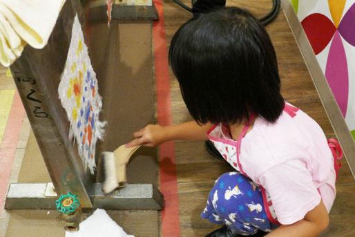 幼稚園児クラスの紙すき体験で、和紙を専用の乾燥機に張って乾燥させます。刷毛でしわを伸ばしているところです。