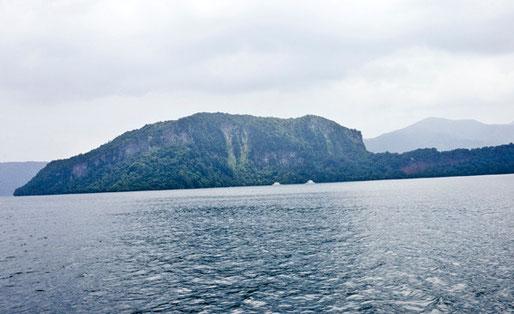 小倉半島の下に見える2隻の遊覧船の右側の近くにその洞窟があります