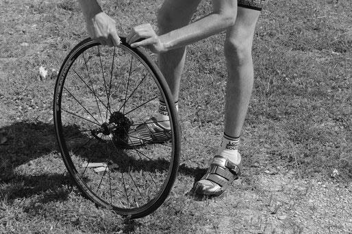 Rennradfahrer der den Reifen abzieht
