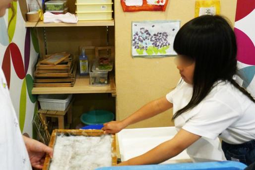 幼稚園児クラスの紙すき体験で、すくった原料から余分な水分を専用の機械を使ってとっているところです。