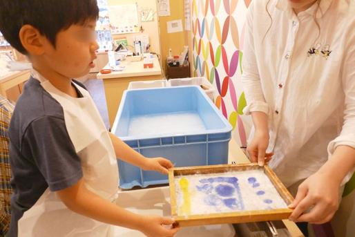 幼稚園児クラスの紙すき体験で、色つけのあとにもう一度吸水を行っているところです。