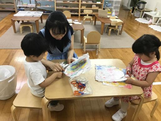 幼稚園児クラスの年少児がモンテッソーリ活動で、つくった和紙でうちわを製作。慎重に和紙をはさみでカットしています。