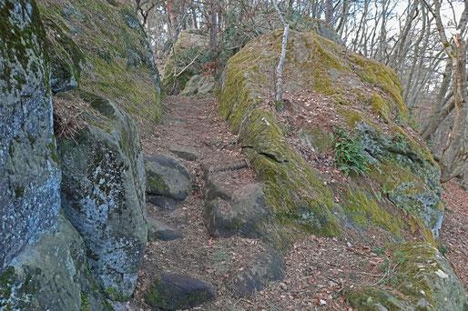 Auf schroffen Felsen wächste Moos. Ein schmaler Weg führt über Steinstufen zwischen Felsbrocken hindurch.