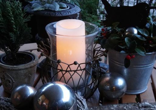 Bild: Winterliche Dekoration im Garten, Kerzenlicht, Tannenbäumchen und Weihnachtskugeln