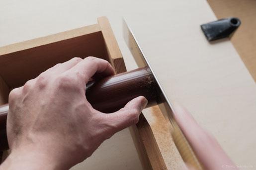 鋸で煤竹の端を落とします。台を置いて水平に