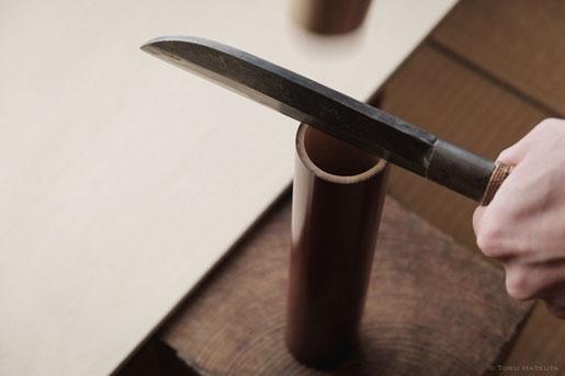 煤竹の筒を半分に割ります。木の台に置いて、鉈と木槌で