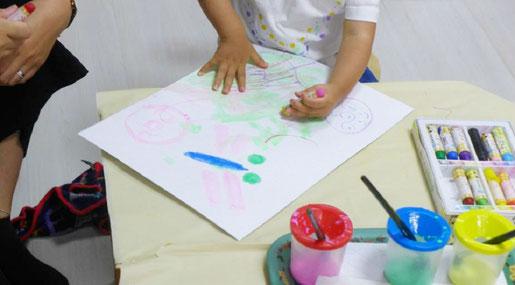 モンテッソーリの活動でステッラコースの1歳児がお母さんといっしょにトンボの絵を描いています