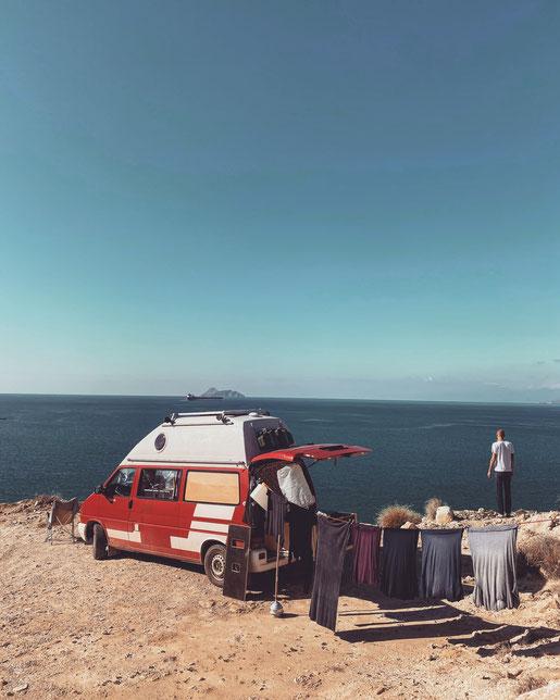 VW Bus mit Wäscheleine steht an der Küste in Griechenland mit Meerblick
