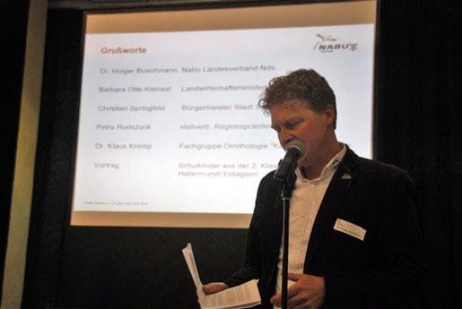 Hr. Buschmann auf einer kleinen Bühne mit einer Präsentation im Hintergrund