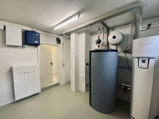 Neuer Heizraum eines iKratos Kunden mit Photovoltaik und Speicher (links) und einer Wärmepumpe (rechts). © iKratos