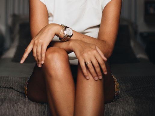 Torso einer Frau mit überkreuzten Unterarmen