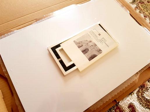 Bild in einer Plastikhülle eingeschweißt, dann auf der Sichtseite mit dünner Polsterfolie abgepolstert