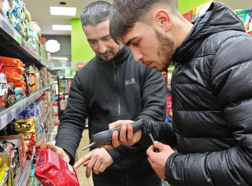 Inhaber erklärt seinem Azubi, wie man Waren scannt