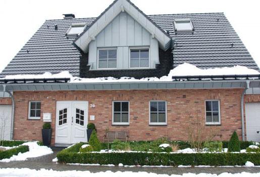Foto: BGL. - Ein sicherer und attraktiver Vorgarten im Winter: Von Schnee geräumt, mit Immergrünen sattgrün und eingerahmt und mit gesunden, ausreichend gegossenen Kübelpflanzen neben der Haustür