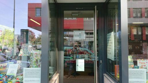 Eingang der Buchhandlung Domstraße (in den Schaufenstern spiegelt sich der gegenüberliegende modernistische Bau)