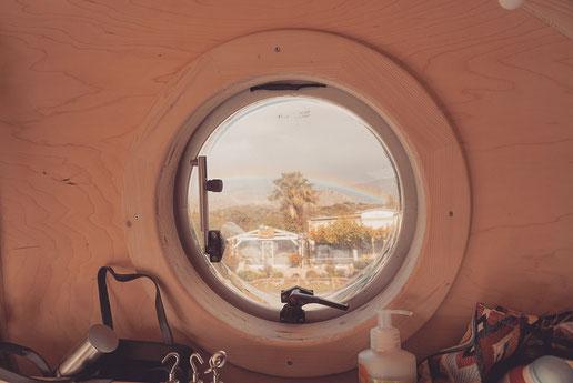 Rundes Fenster mit Holzrahmen Ausblick aus VW Bus
