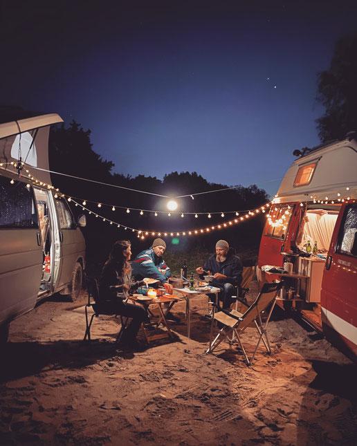 Eine Frau und zwei Männer sitzen abends an einem Tisch im freien zwischen zwei VW Busse