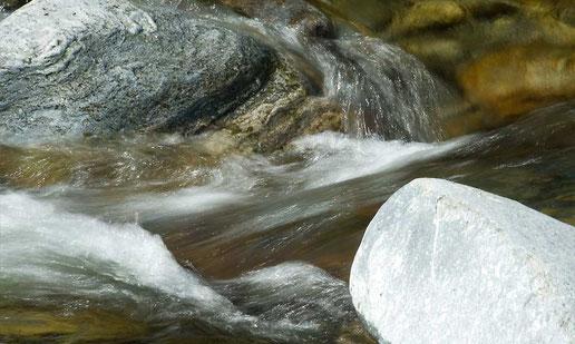 Wasser rauschend durch Enge zwischen Steinen