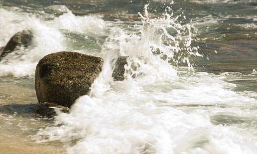 zerschellende Wellen an einem grossen Stein am Strand