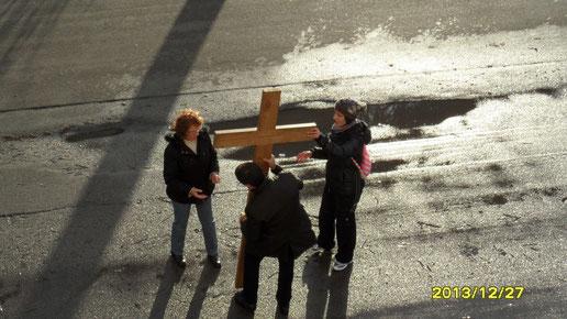 Siamo arrivati al rione Paradiso. Un momento di sosta prima di riprendere il cammino. Nino aiuta a sistemare per terra la croce che fin qui è stata trasportata a spalla.