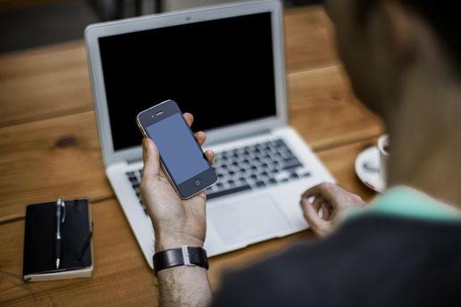 Mann mit Laptop und Handy in der Hand