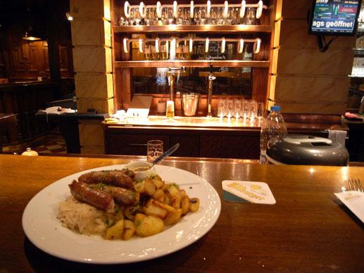レストランにて  奥にいろんな種類の生ビールが並ぶ 食べ物はソーセージの盛り合わせ