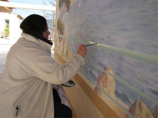 Geneviève peint les effets de lumière et d'ombres sur la fausse balustrade de la fresque à Nans les Pins