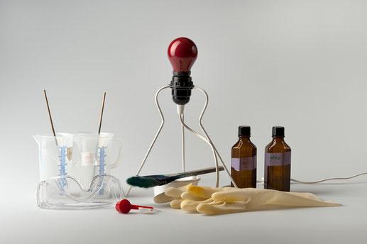 Eliana Bürgin | Utensilien für die Zubereitung der Cyanotypie. Chemiekalien (Ammoniumeisen(III)-Citrat und Kaliumferricyanid), Messbecher, Messlöffel, Pinsel, Handschuhe, Schutzbrille, Dunkelkammerbirne und Braunglasflaschen
