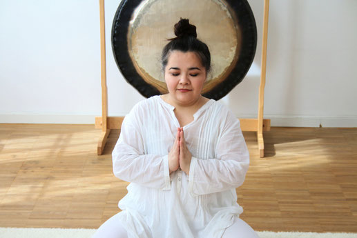Frau in Weiß sitzend und meditierend. Ein Gong im Hintergrund.