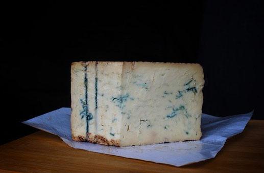 une part de fromage bleu présenté sur un papier bleuté le tout sur une table en bois