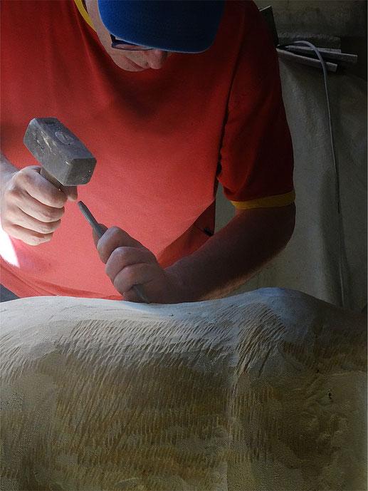 Hammer und Meißel in den Händen eines Bildhauers.