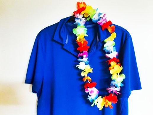 Ein Hawaiihemd hängt am Türhaken mitsamt einem Blumenkranz. Dieser Modestil aus Polynesien steht für bunte Farben und gute Laune.
