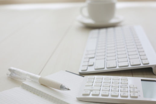 デスクに置かれた白色のビジネスグッズ。パソコンのキーボード、方眼紙ノート、ボールペン、電卓。カップ&ソーサ。