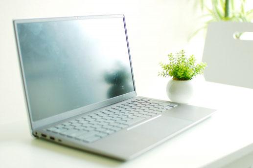オフィスのデスク。方眼紙ノートにメモをとる指先。タブレット、イヤホン。