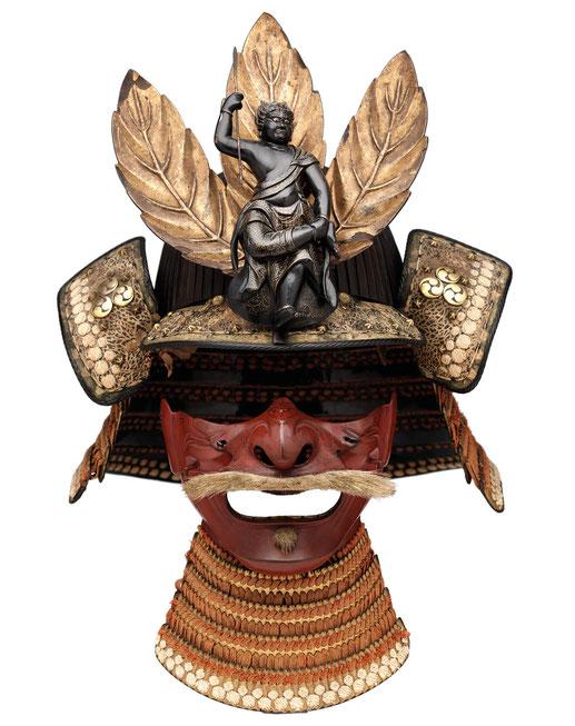 Helm und Halbmaske eines Samurai, spätes 16. Jahrhundert. Den Helm ziert eine Figur des Gottes der Weisheit vor drei goldenen Blättern.
