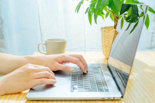 ノートパソコンで作業中の女性の指先。傍らにマグカップ、ノート、ペン。