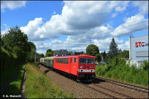 Am 8. August 2021 genießt die Lok, im ehem. Übergangslack der DR, Museumsstatus. Mit einer Wagenüberführung ist sie von Zwickau nach Leipzig-Plagwitz unterwegs und durcheilt hier Chemnitz-Schönau