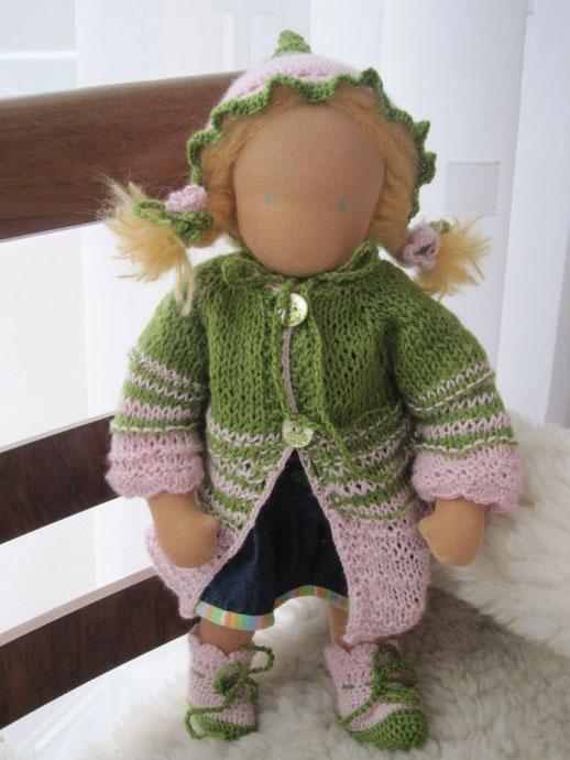 Anna trägt einen Mantel und passende Schühchen und Blütenkelchmütze aus grünem pflanzengefärbtem Schurwoll-Rami-Garn und rosa Alpaka-Seidengarn mit den hübschen Froschkönigknöpfen