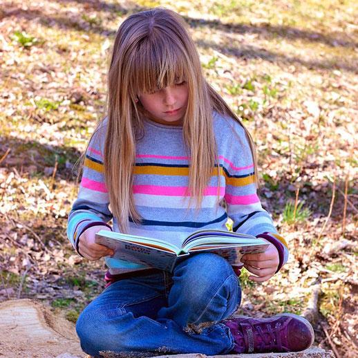 Mädchen liest ein Buch in freier Natur.