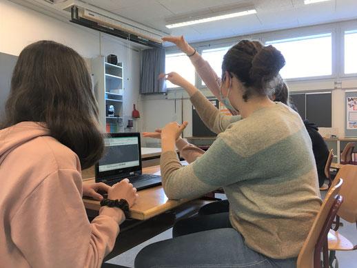 Drei Schülerinnen besprechen ihr Ausstellungskonzept.