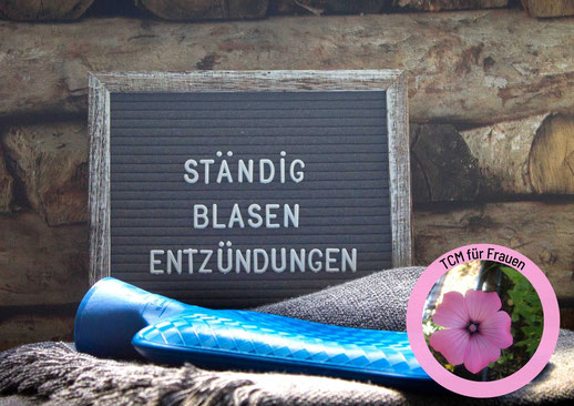 rote Wolldecke, darauf liegt ein rot weiß kariertes Kissen, eine rote Wärmflasche und Fell-Pantoffeln