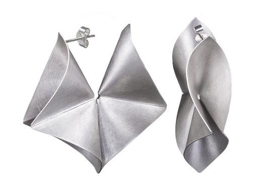 Der Ohrschmuck YARA aus Silber ist außergewöhnlich und auffallend. Wie eine große Creole umschließt er das Ohrläppchen und fasziniert dabei mit seiner besonderen, plastisch ausgearbeiteten Form. Das Silber schimmert und leuchtet, wenn Sie sich bewegen