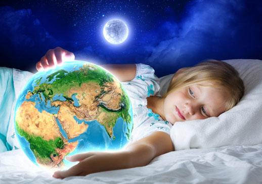 Niña rubia en la cama con la bola del mundo en sus manos